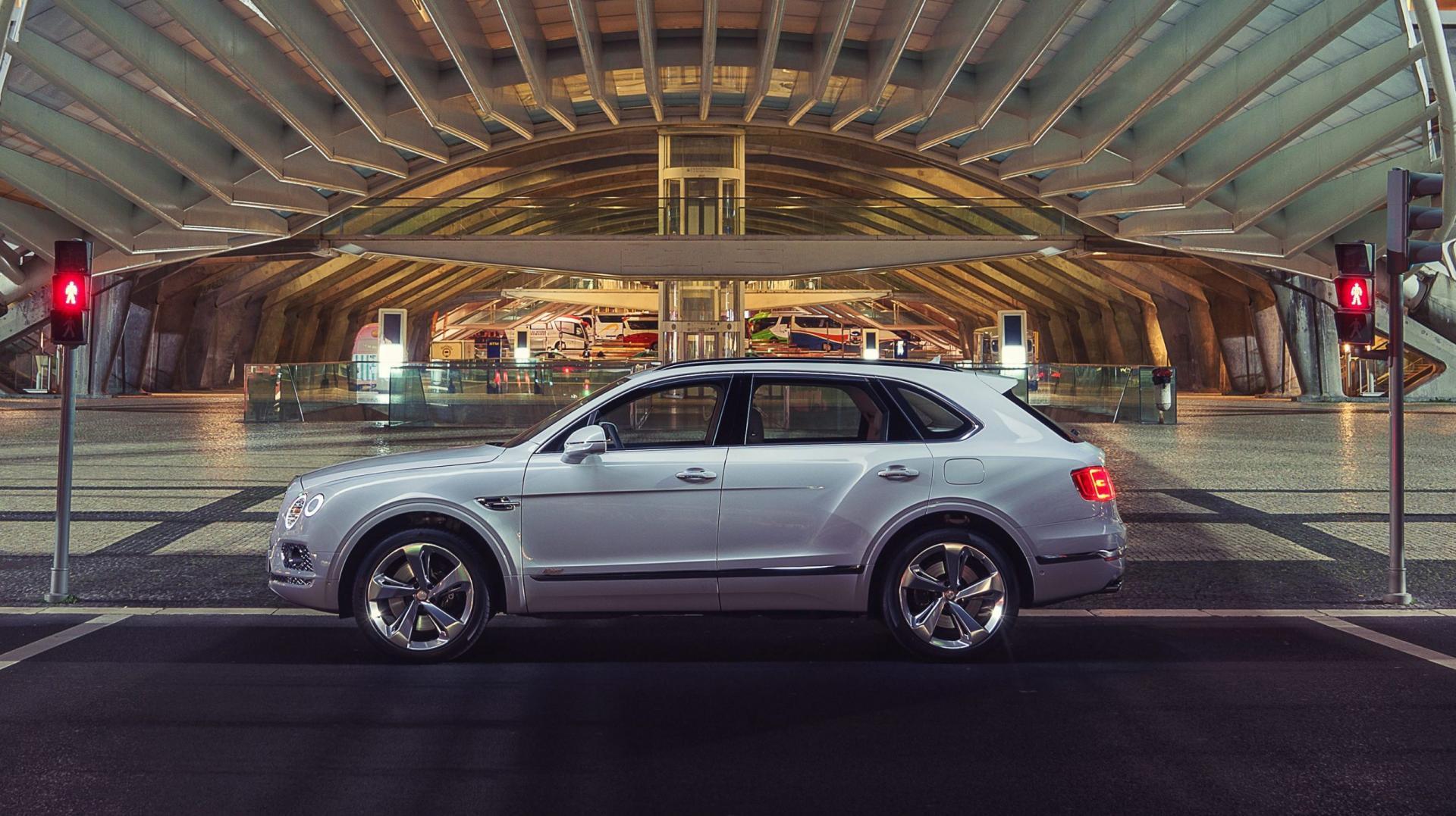 Bentley Bentayga Hybrid onder boog donker