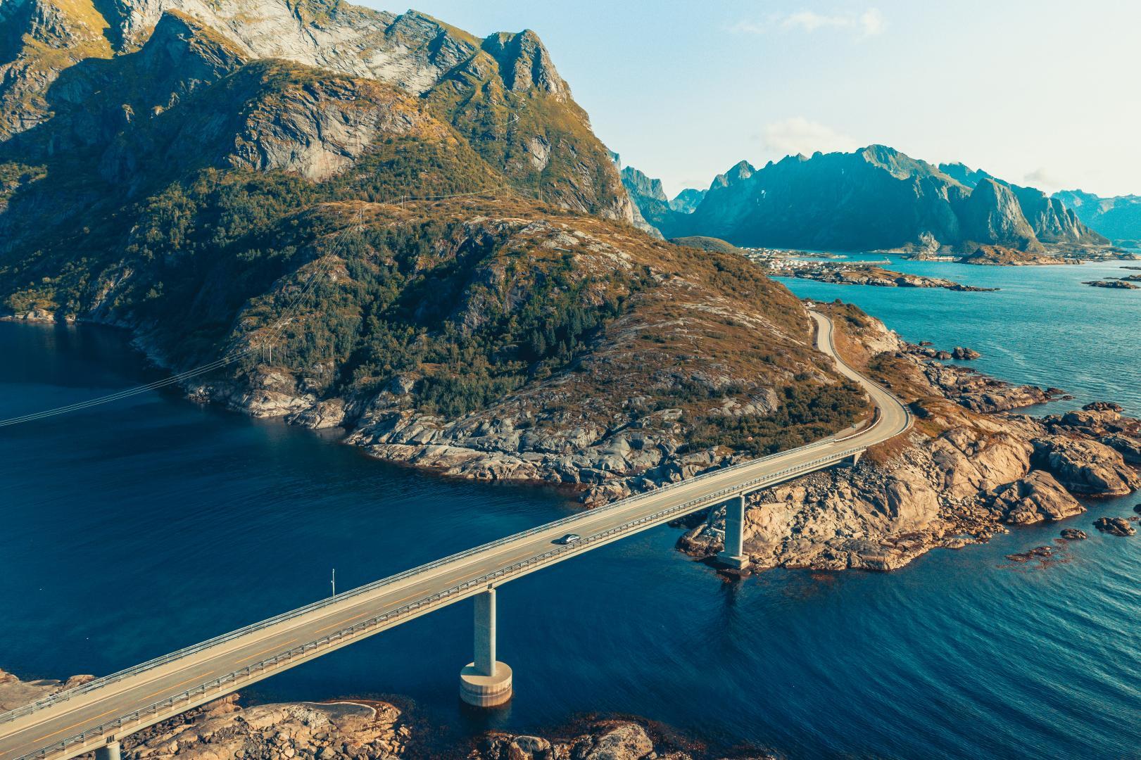 Polestar 1 rijdend op lange brug met landschap