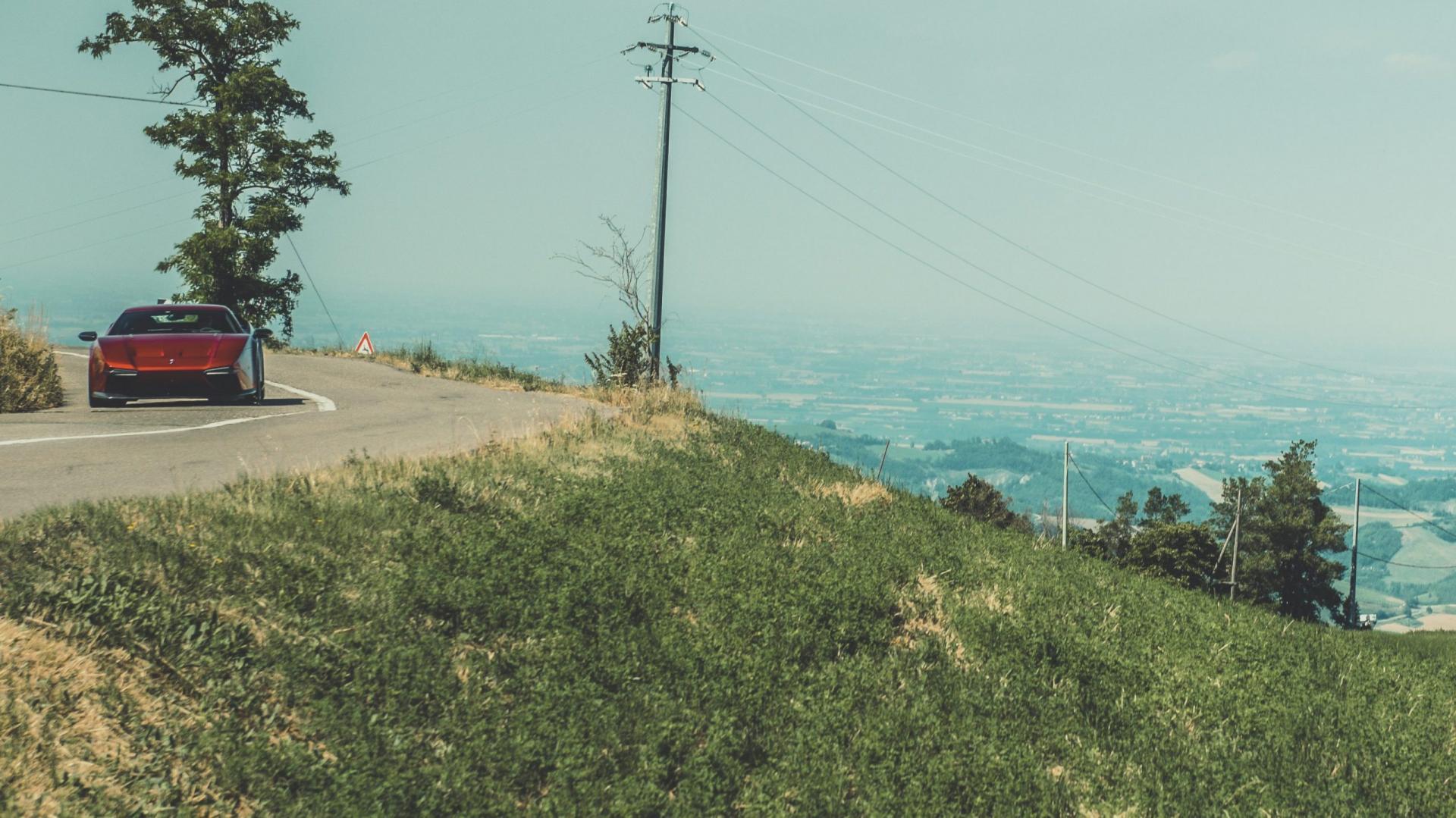 Ares Panther zoomed rijdend in bocht met landschap