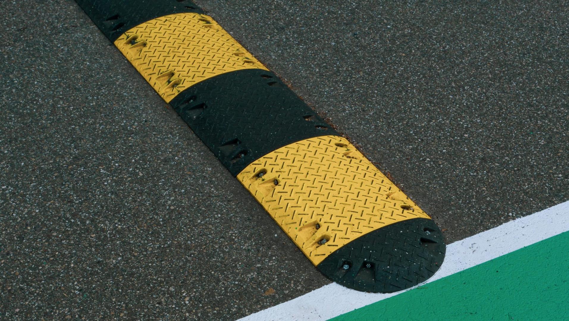 Drempel langs groene weg met witte lijn