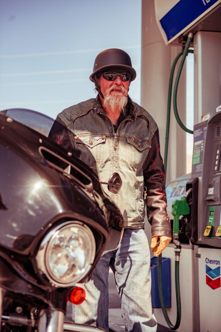Man met helm op bij tanktstation met zijn motorfiets