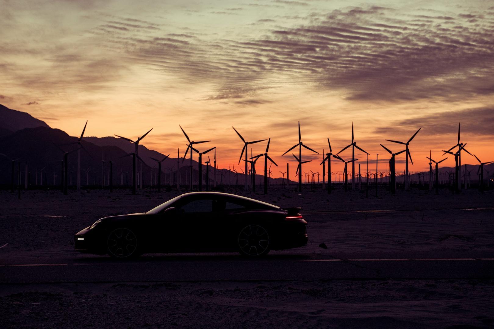 Porsche 911 Turbo S (992 2020) bij windmolens bij zonsondergang