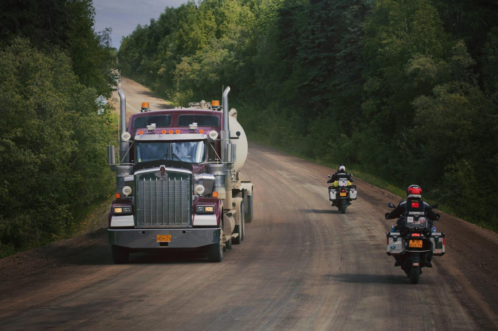Kenworth-vrachtwagen op onverhard met motorrijders