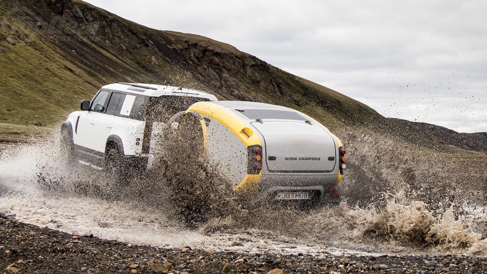 Mink minicaravan met Defender door de modder