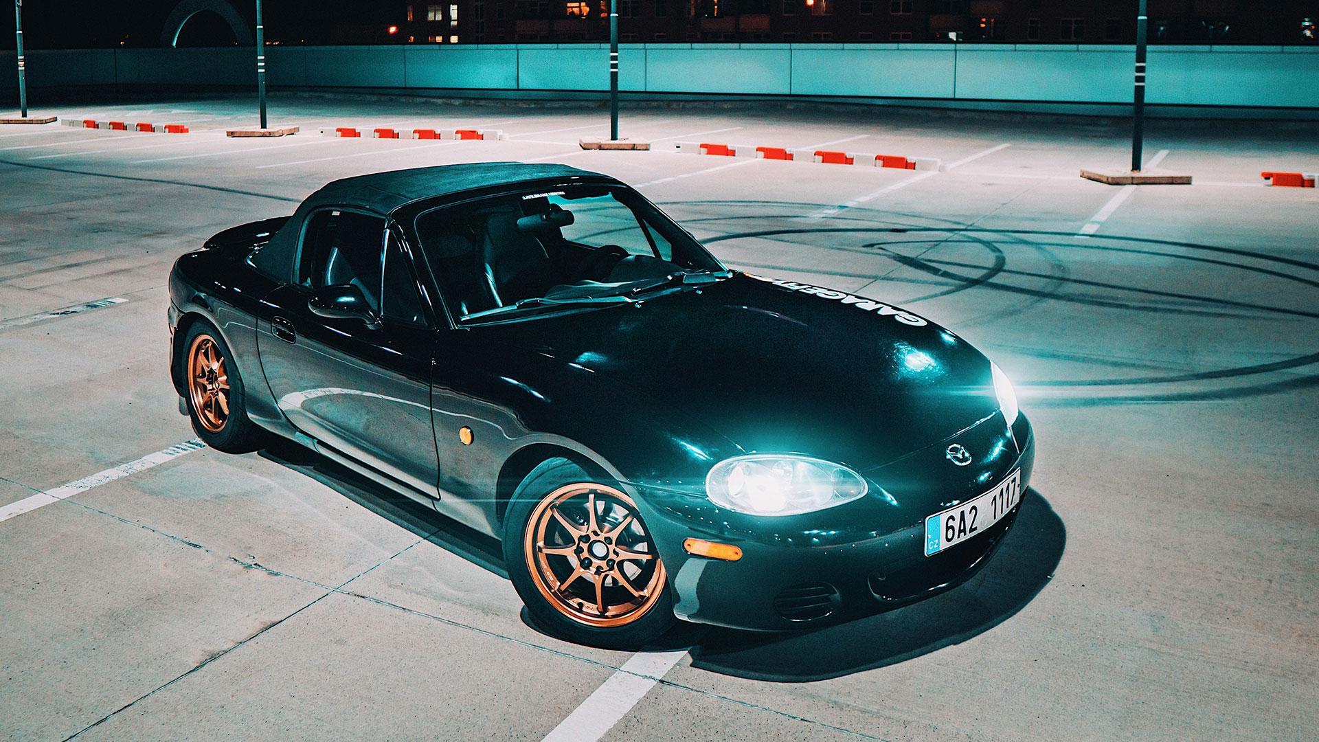 Mazda MX-5 NB met slipsporen op het parkeerterrein