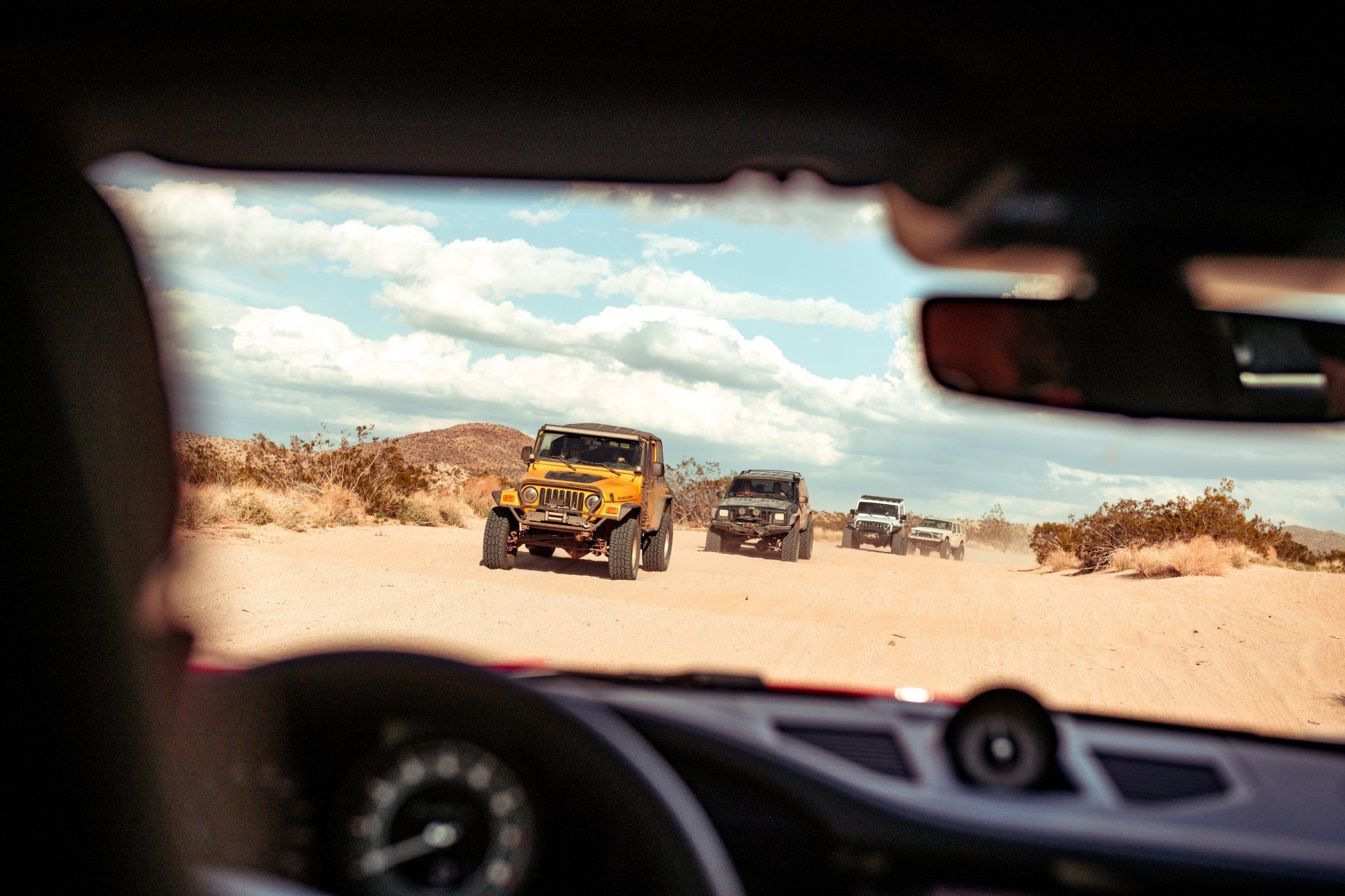 Jeep Wrangler en Cherokee gezien vanuit Porsche 911 Turbo S in woestijn